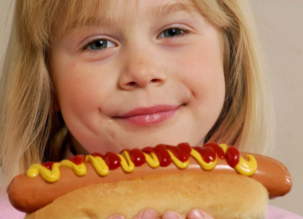 ילד אוכל נקניקיה בלחמניה עם חרדל וקטשופ